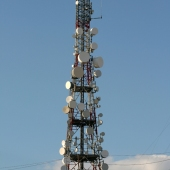 communications antena tower full of dishes with sky background